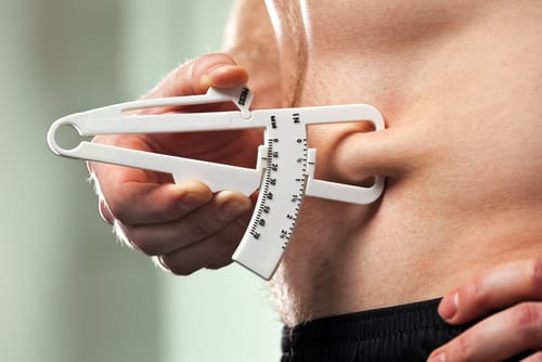Young man is measuring his body fat with calipers-img-blog
